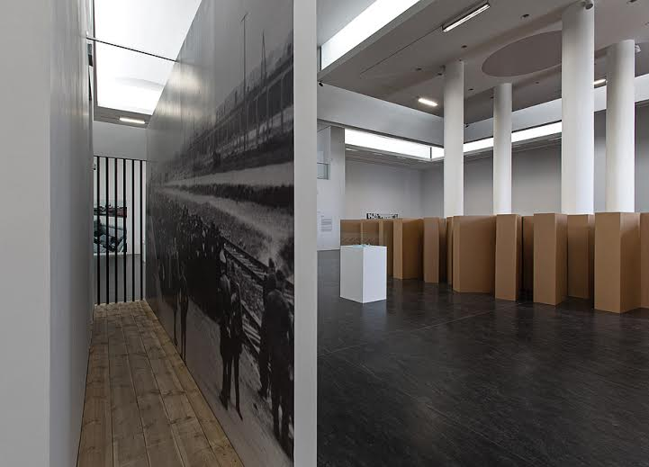 Gustav Metzger, Exhibition view in the Centre of Contemporary Art Znaki Czasu in Toruń, 2015, on the left: Historic Photographs: The Ramp at Auschwitz, Summer 1944, 1998, b&w photograph, drywall, wood, steel, 330 x 663 cm, Courtesy of the artist, photo: Wojciech Olech