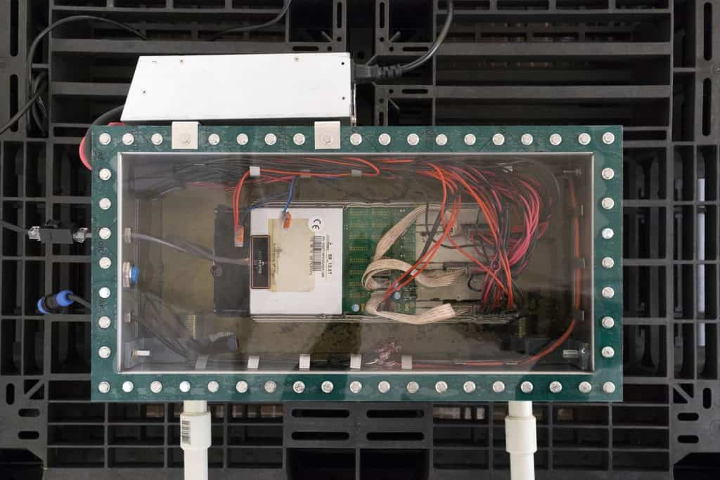 Jan Domicz, Untitled (Greenhouse 18m2) 2019, AntMiner, internet connection, oil, pump, heaters, HeatMiner, foil, pcv pipes, sliding doors