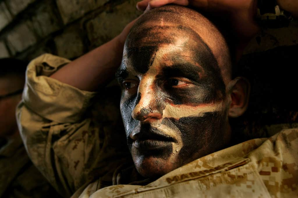 Carolyn Cole, A US marine is covered in camouflage face paint during the battle for Najaf, Iraq, where American forces spent weeks bombing and fighting their way to the city's holy Imam Ali Shrine, before negotiating an end to the fighting, Najaf, Iraq, August 2004. © Carolyn Cole / Los Angeles Times